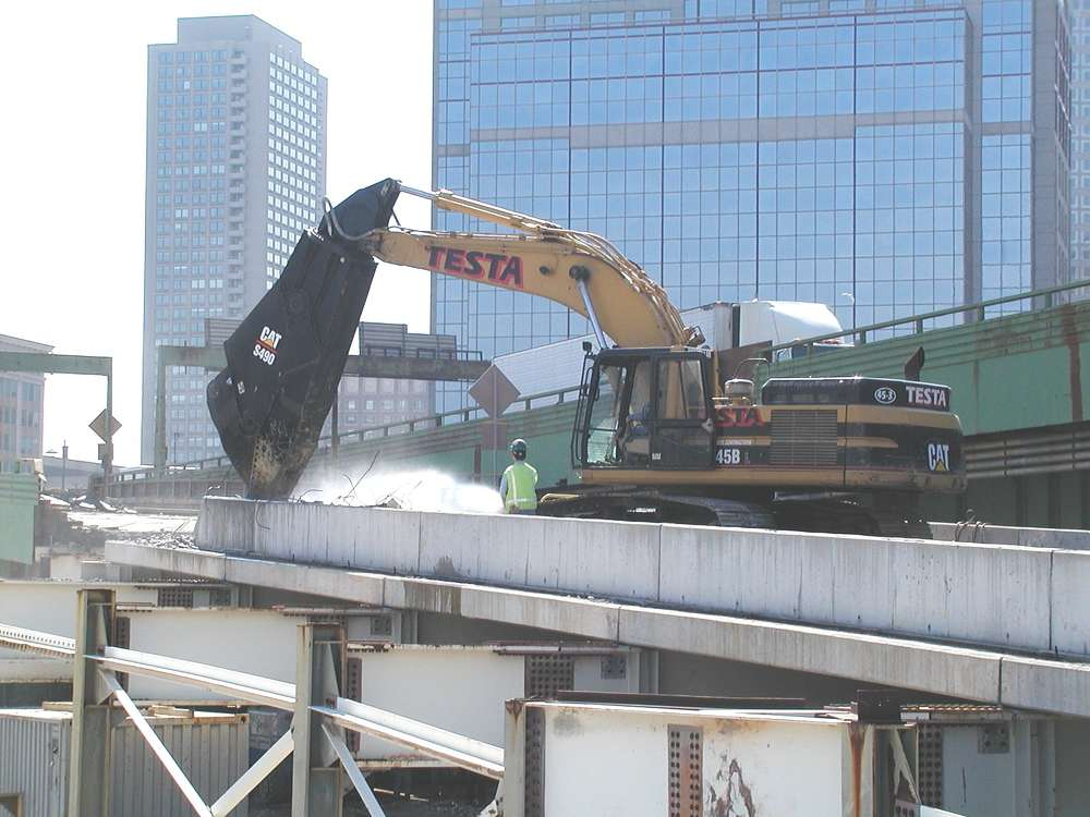 A Testa crew uses a Cat excavator equipped with a massive shear to demolish a temporary ramp structure near the Central Artery.