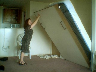 woman folding murphy bed up into wall