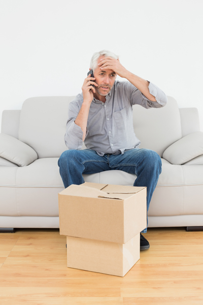 rental scam man sitting on the couch with box upset talking on the phone