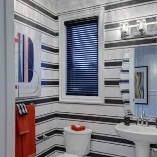 Dans cette salle de bain, nous avons créé un contraste visuel avec un papier peint fait de larges bandes horizontales, de Graham and Brown.