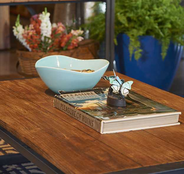 A rustic coffee table and open shelving from Artemano is lightened and brightened with summery blue ceramicware from HomeSense.