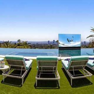 Outdoor pop-up theatre behind the 85-ft., glass-tile infinity swimming pool