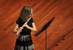 a female Community Music students plays flute in a recital