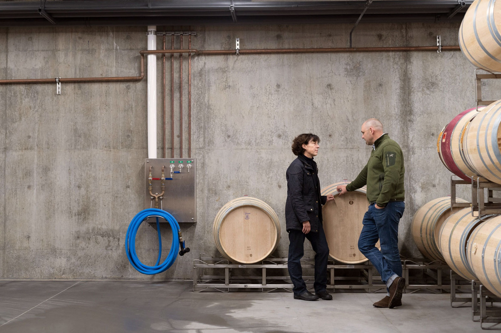 Françoise Peschon and Nigel Kinsman conversing in the barrel room at Wheeler Farms Winery, where Accendo Cellars' wines are made and tasted.