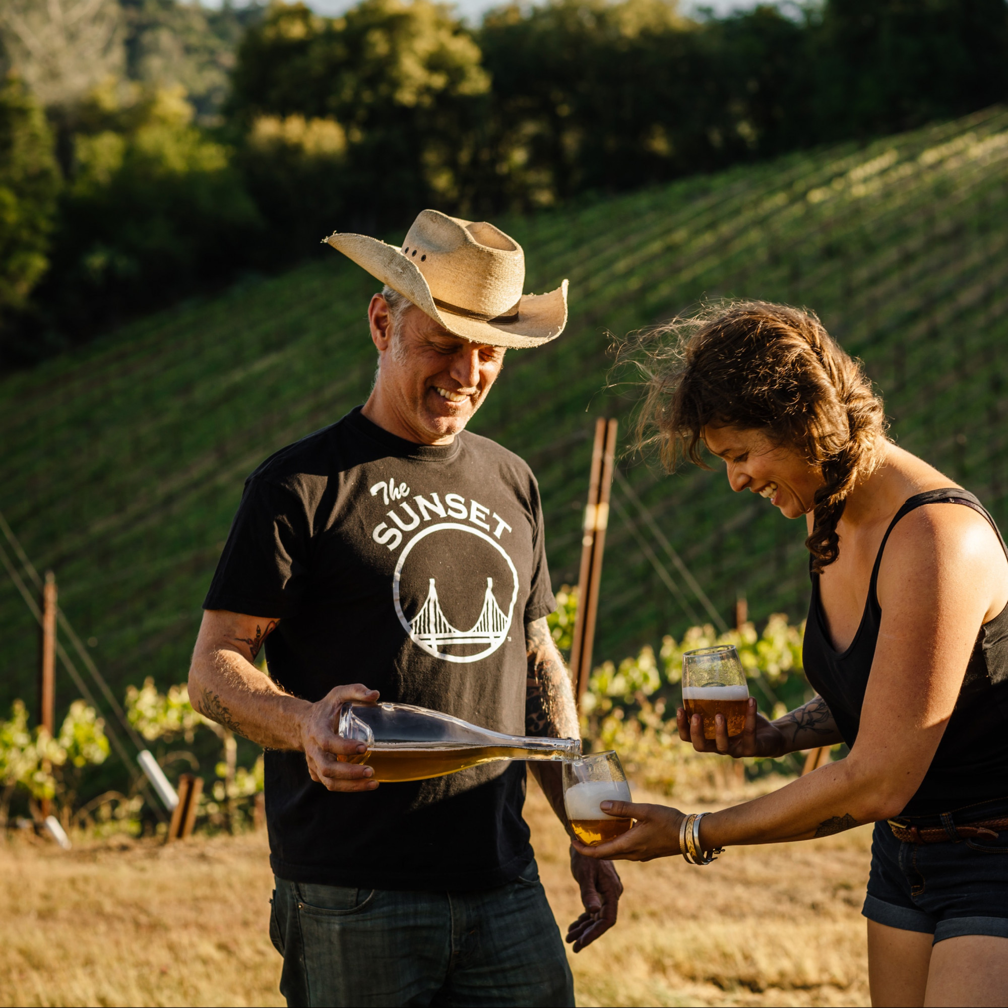 Winemaker Matthew Rorick pours a glass of sparkling wine in the vineyard.