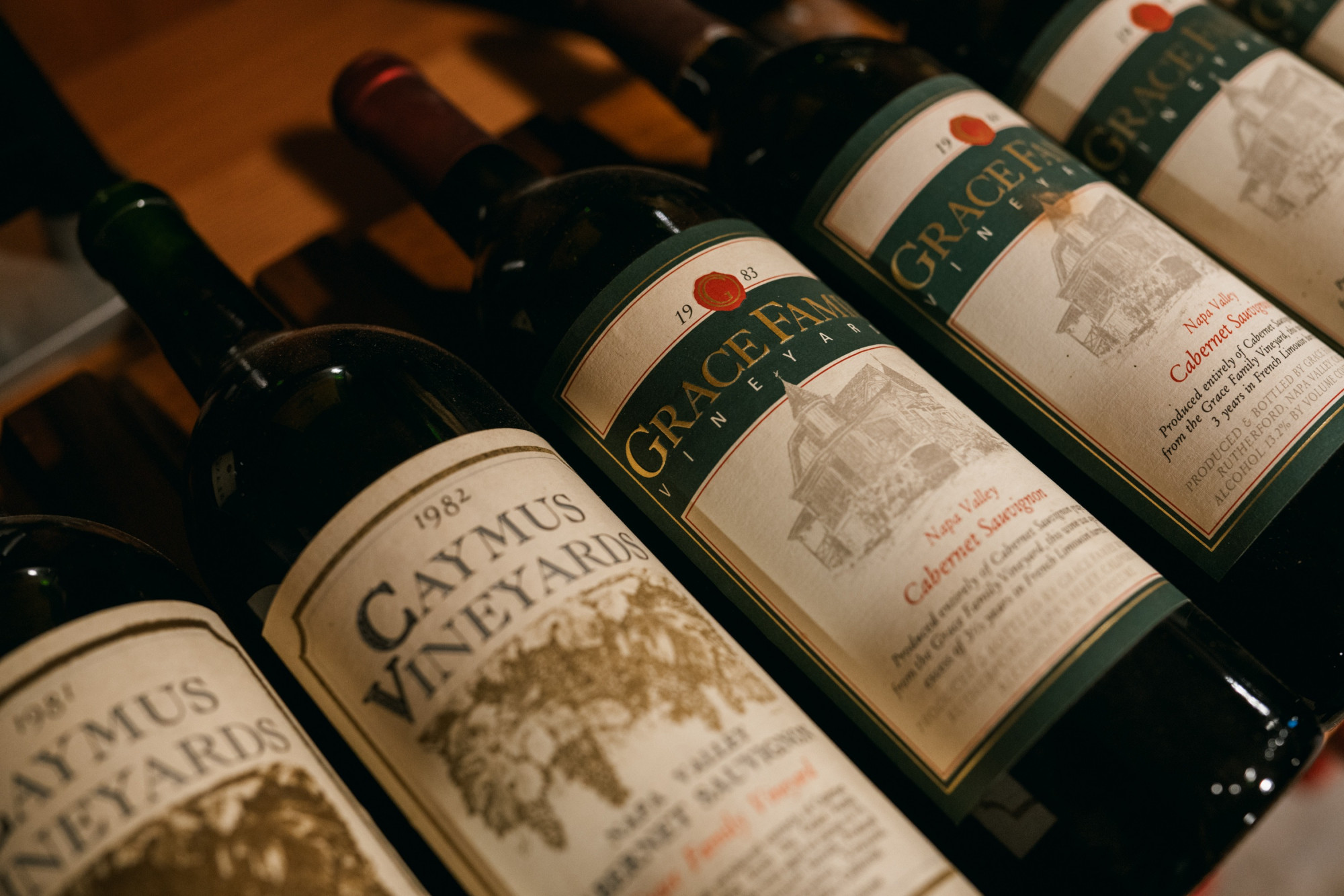 Bottles of Caymus and early Grace Estate wines in the cellar
