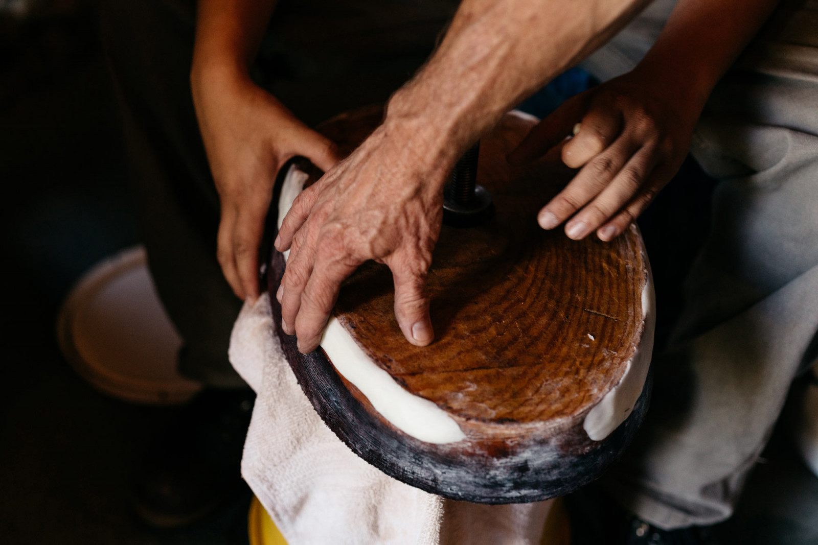 Close-up of two sets of hands working on barrels