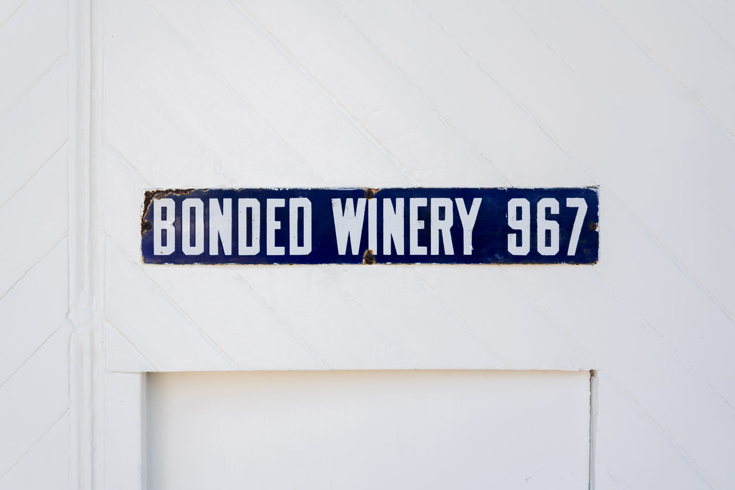 https:Close-up of the Bonded Winery 967 sign above the old cellar door