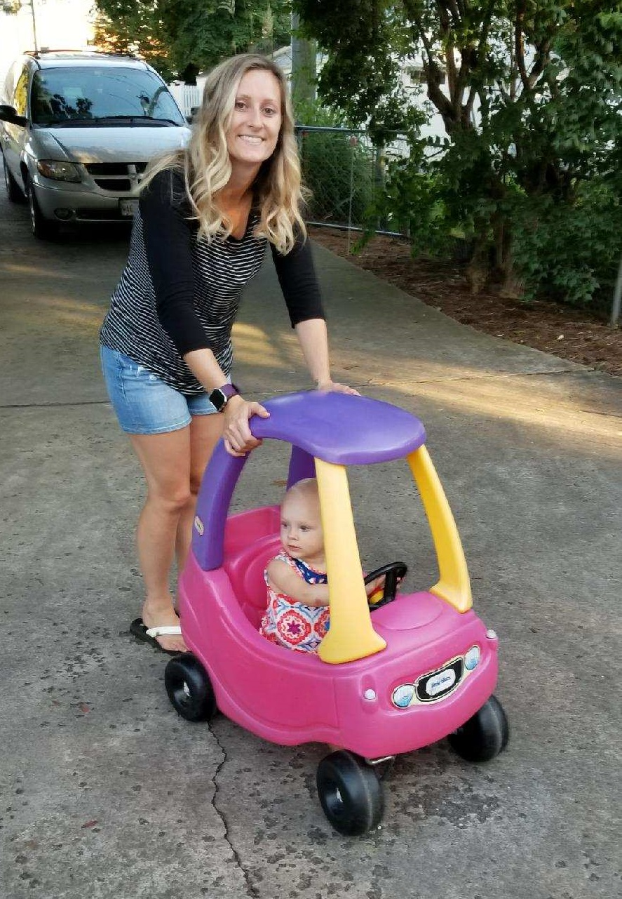 Shana with her daughter in a play car