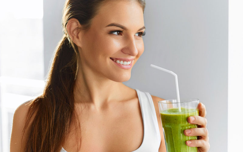 woman drinking smoothie with a straw