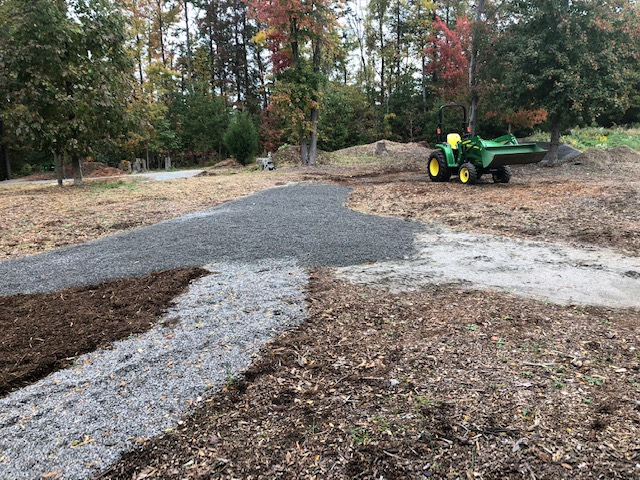 A tractor laying gravel out along paths