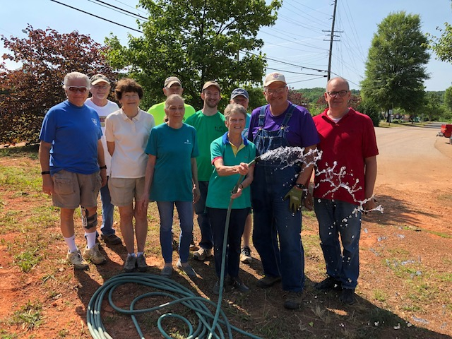 A group of 10 people holding a running hose