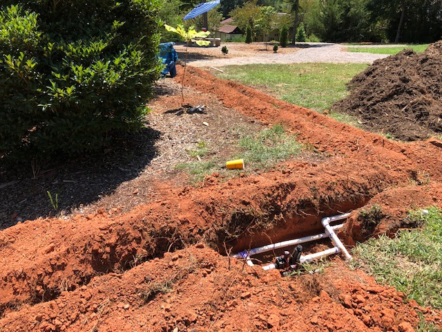 White pipes laid in a deep trench in the ground