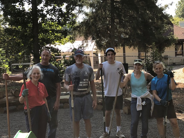 A group of 6 people with gardening tools