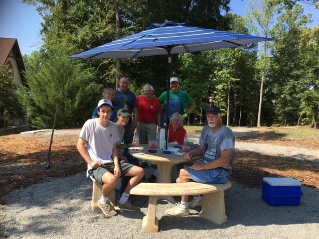 8 volunteers underneath a picnic table