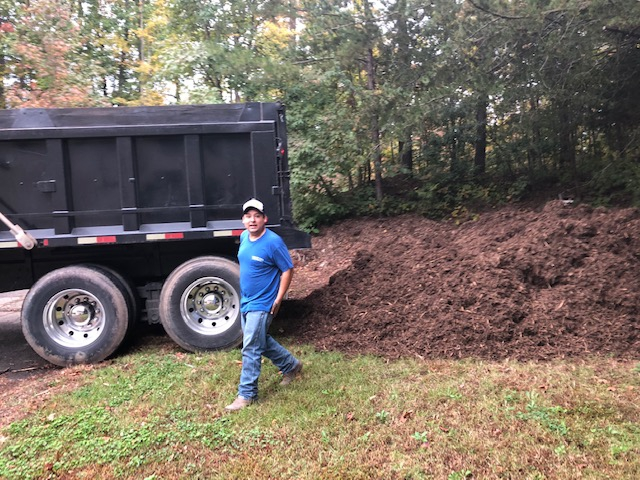 A person standing in front of a large truck and mulch pile