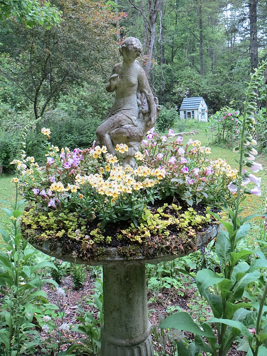 Birdbath repurposed as a planter with a fairy sculpture in the c