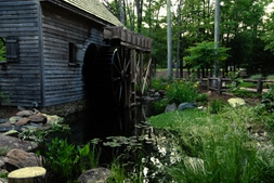 the front of the water garden featuring a pond and water wheel