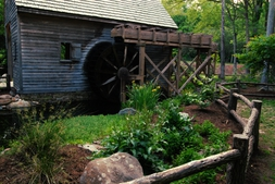 the side of the water garden featuring a pond and water wheel