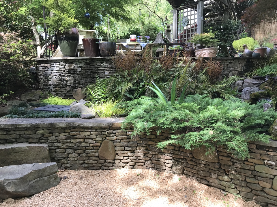 a patio garden incorperating stone walls and rocks