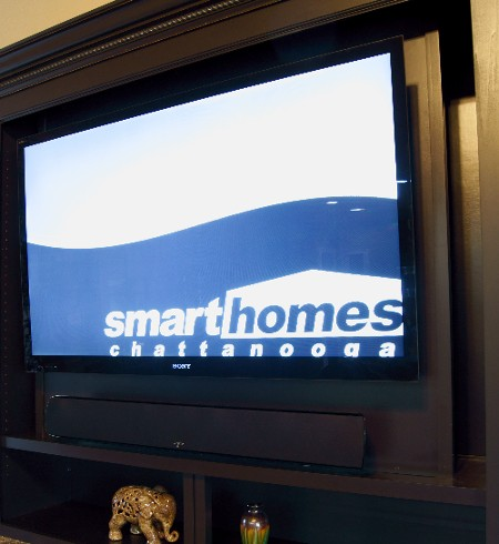 A soundbar used with a flat panel TV in a built-in wall cabinet.