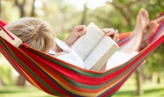 Woman reads on hammock stock