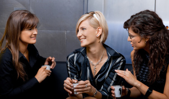 Women talking over coffee stock