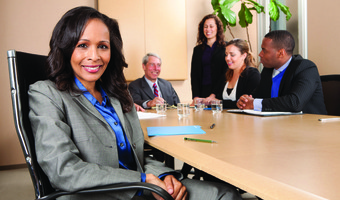 Woman smiling during meeting stock