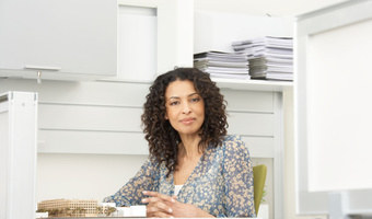 Businesswoman at desk smiling thinkstockphotos