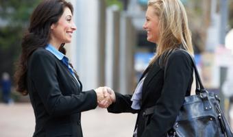 Women colleagues shake hands stock