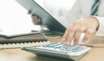 Woman using calculator istock