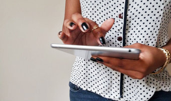 Black woman holding ipad createherstock
