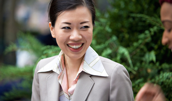An attractive asian woman dressed in business attire laughing at the words of her business associate hthx7hwabo
