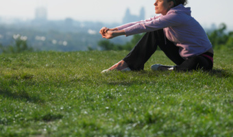 Woman sits outside on grass