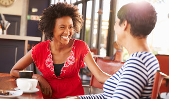 Women laughing talking coffee shop stock
