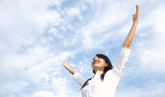 Woman with hands in air outside stock