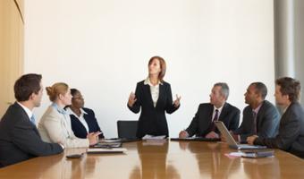 Businesswoman leading board meeting stock