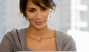 Woman smiling at computer thinkstockphotos