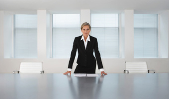 Powerful woman standing behind table thinkstockphotos