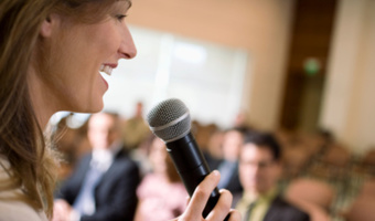 Woman speaking front of crowd stock