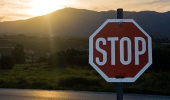 Stop sign by mountains sunrise stock