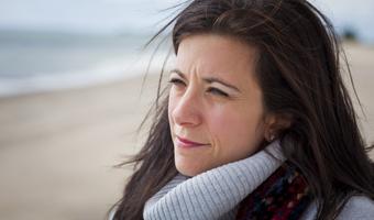 Thoughtful woman on beach thinkstock