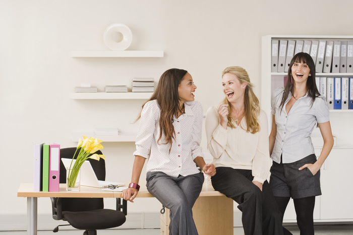 Businesswomen laughing in office