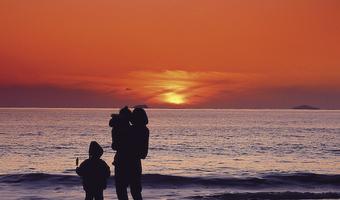 Sunset over ocean mom kids