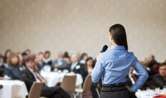 Public speaking woman in front of a people