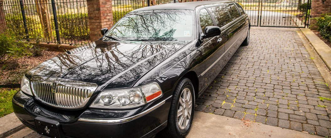 Lincoln Town Car Limousine in front of a gate
