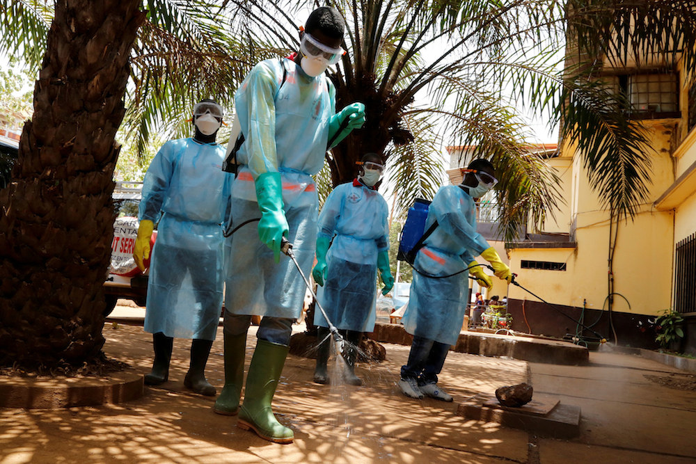 Ebola, medical team disinfecting spray on sidewalk | eMedCert