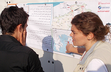 A woman points to a map on a banner while a couple looks on.