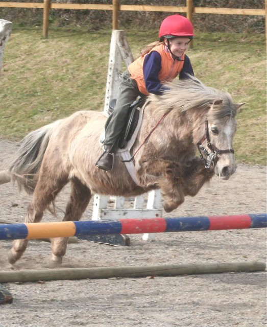 Five year old Holly on 27-year-old, 11-hand Buie (short for Drambuie), jumping her first proper fence. Photo by William Micklem.