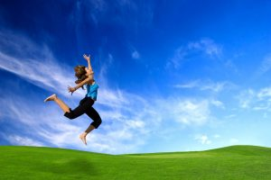 woman jumping in the air with deep blue sky and green grass background